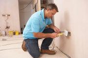 Un homme teste un système électrique avec un multimètre